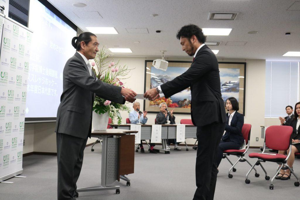 松浪健四郎氏から奨学金賞状を受け取る奨学生